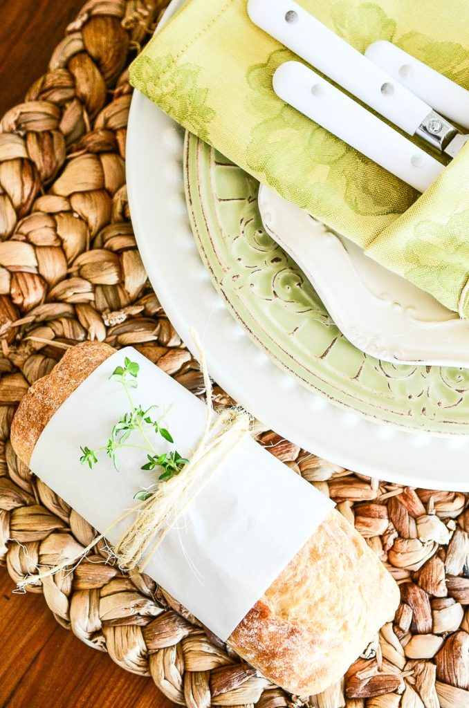 green and white stack of dishes with a mini loaf of bread next to it