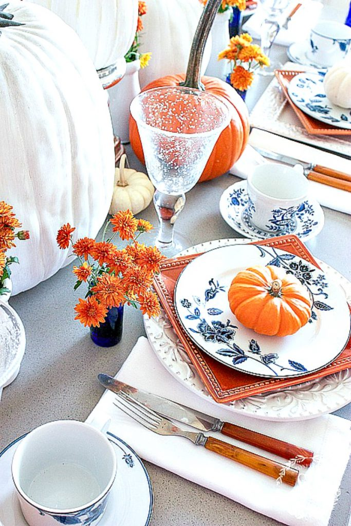 blue, white and orange place settings with an orange pumpkin atop each