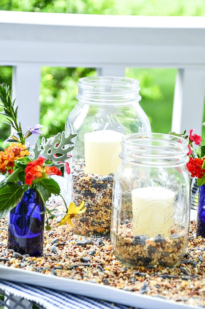 mason jar lanterns and little vases of garden flowers on a white platter