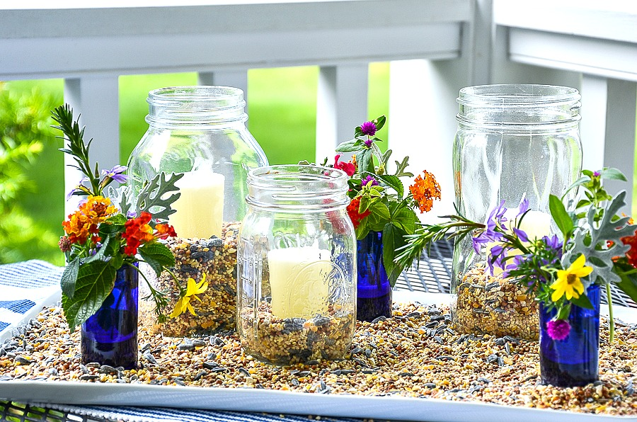 a trio of mason jar lanterns on a white tray