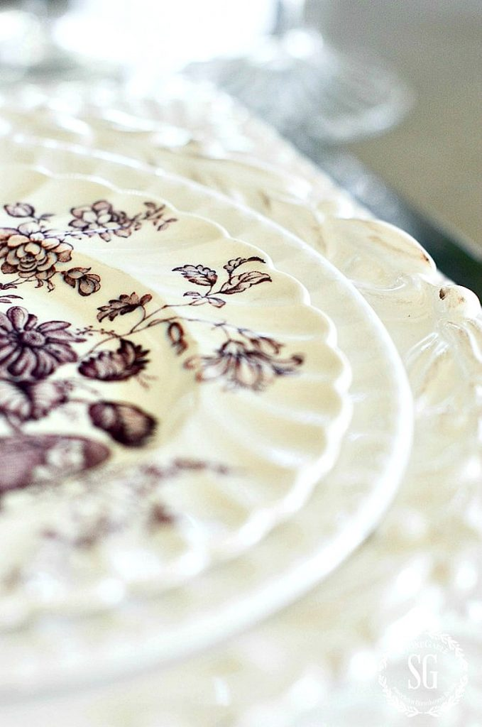 violet and white transferware plate with a scalloped edge