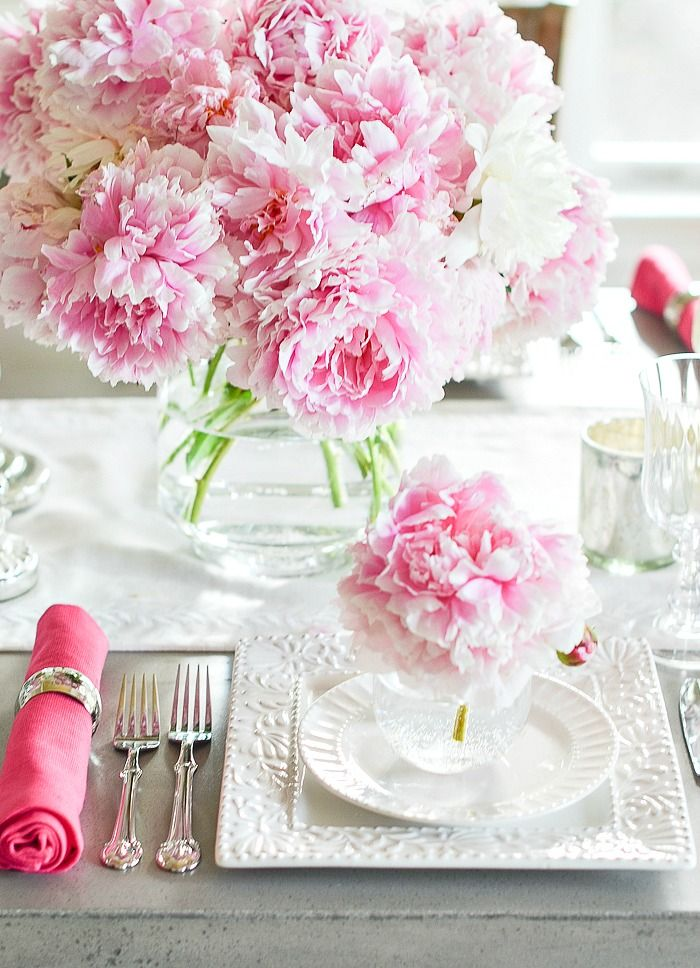 big vase of pink peonies next to a single bloom in a small glass