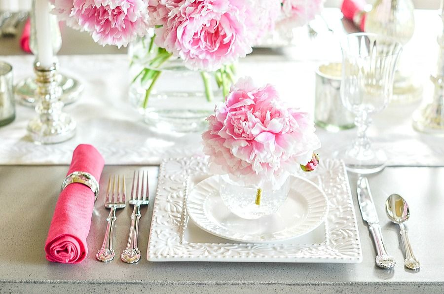 white dishes on a table with pink peonies and hot pink napkins