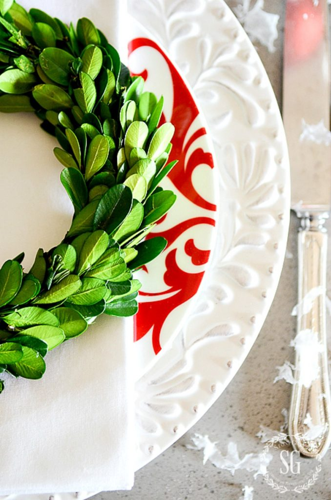 boxwood wreath on top of a red and white stack of dishes