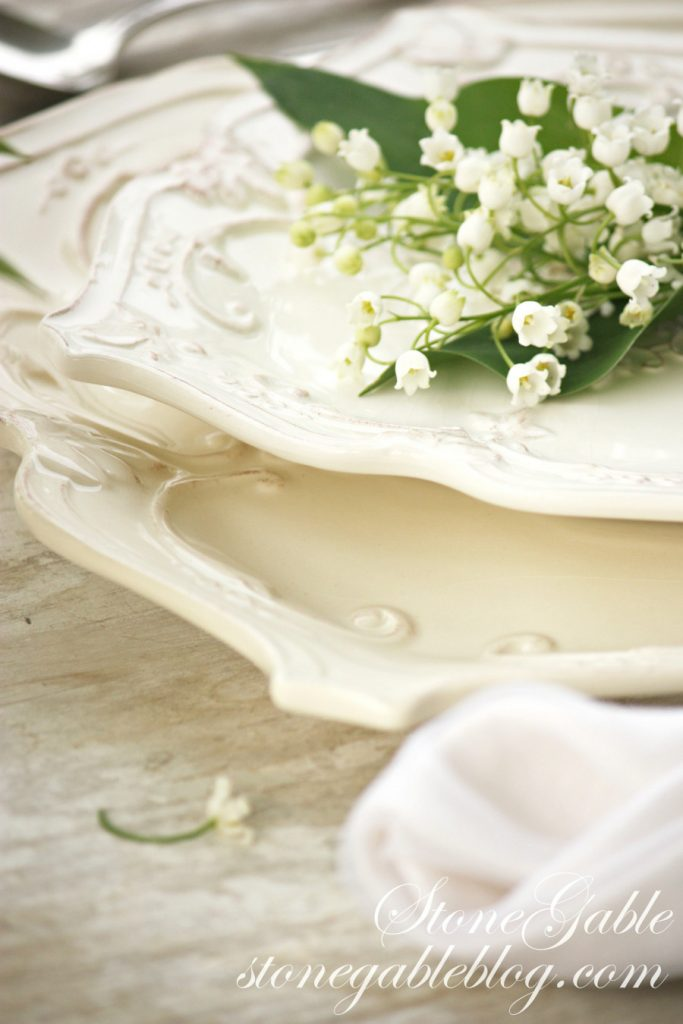 white dishes with scrolled edges with a bundle of lily of the valley on top