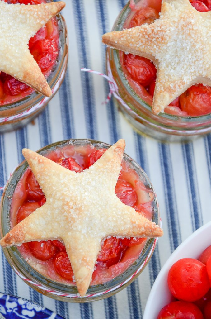 little cherry pies in mason jars with pie dough stars make a delicious summer dessert