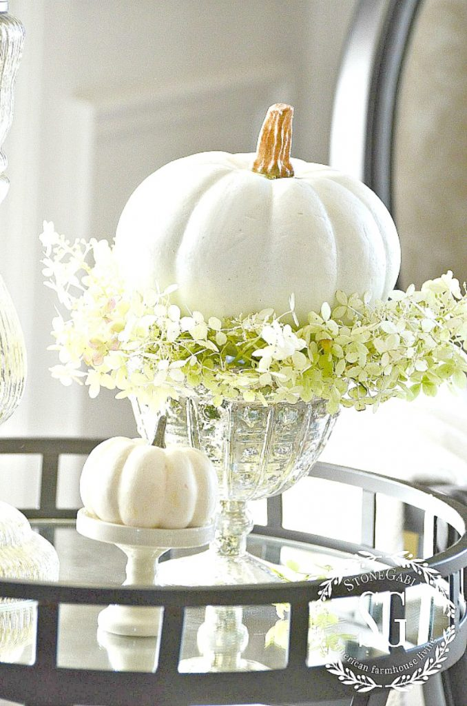 white dried hydrangeas in a mercury glass footed bowl with a tiny white pumpkin on top