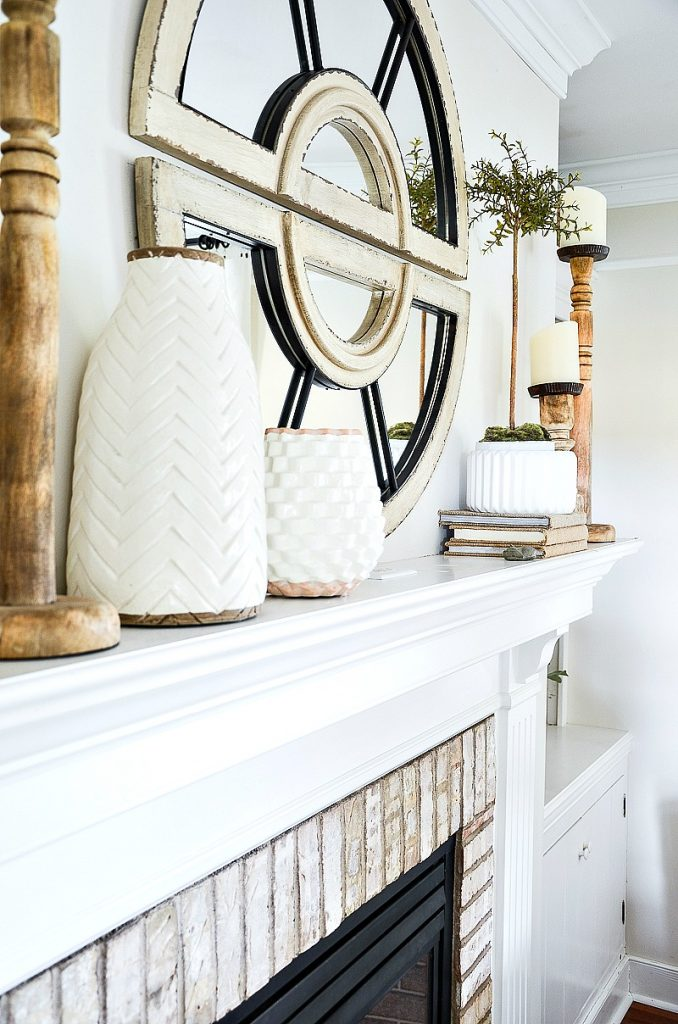 long decorated mantel with white pottery and wooden candlesticks
