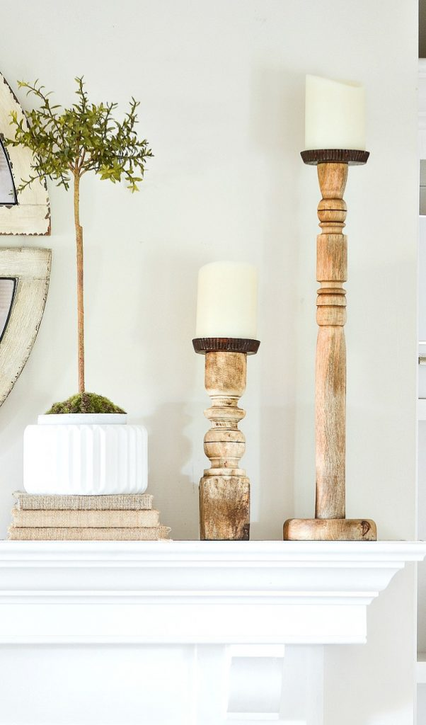 tall candlesticks on a decorated mantel