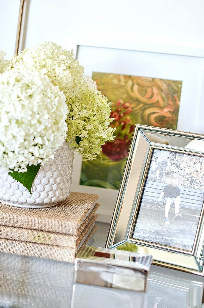 vase of hydrangeas, a silver picture frame and a small silver box on a round glass nightstand.