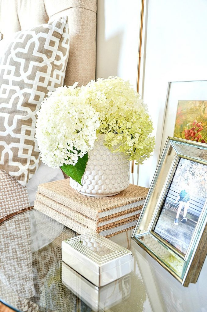 white hydrangeas on a round glass nightstand