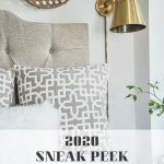 gold sconce in bedroom by bed is a lighting trend for 2020