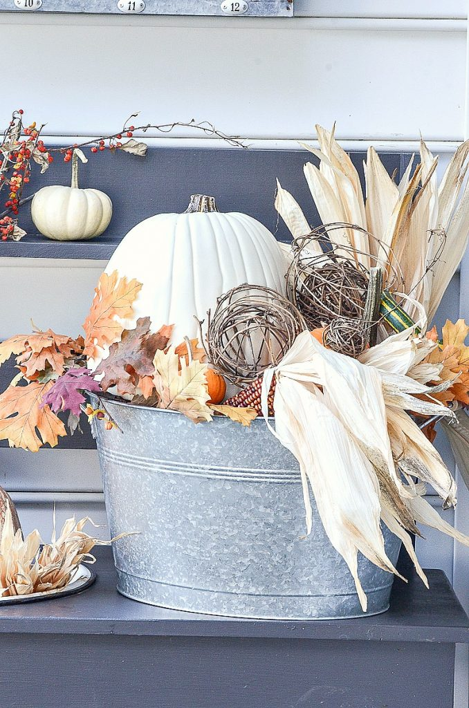 galvanized bucket filled with fall elements like pumpkins and corn