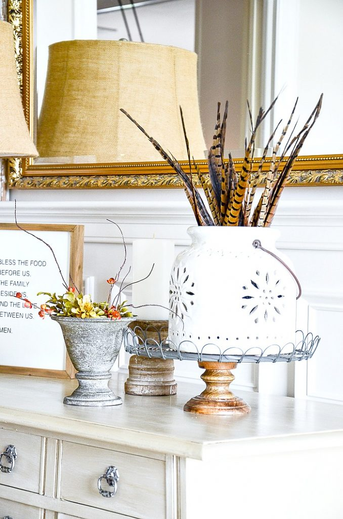 white pottery lantern filled with pheasant feathers fo fall decorating