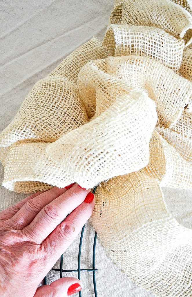 weaving the burlap ribbon on a wreath frame
