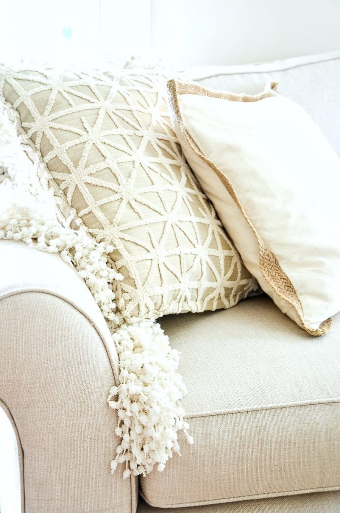 neutral pillows and throws on a sofa in the living room
