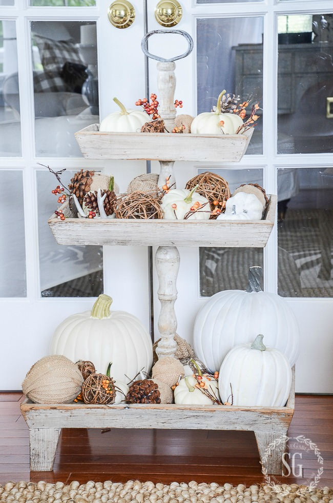 large wooden tiered tray filled with white pumpkins and other fall elements