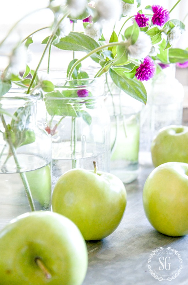 kitchen table vignette with green apples and mason jars with flowers