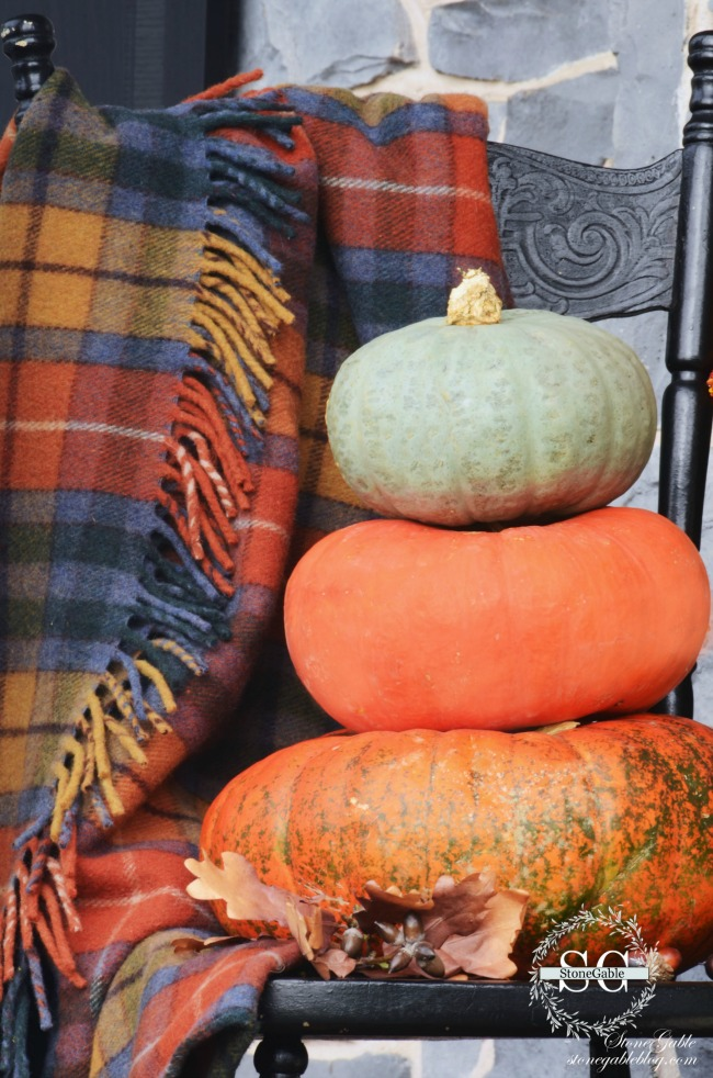 a trio of pumpkins stacked on top of one another on the front porch