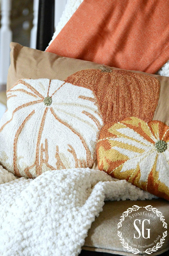 three pumpkins embroidered on a pillow