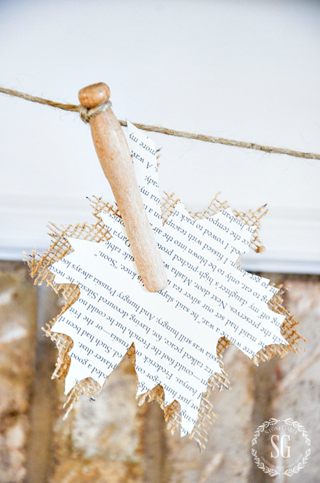 cut out burlap and book page leaf held on a garland with a clothespin