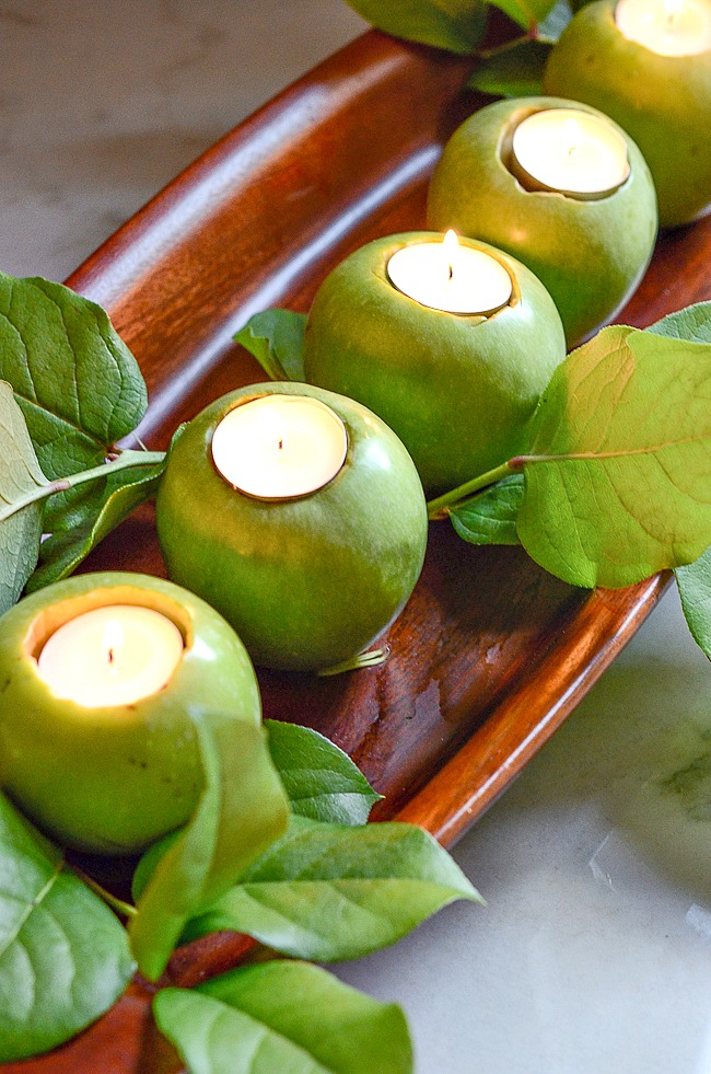 fall centerpiece of apples with candles in them in a dough bowl