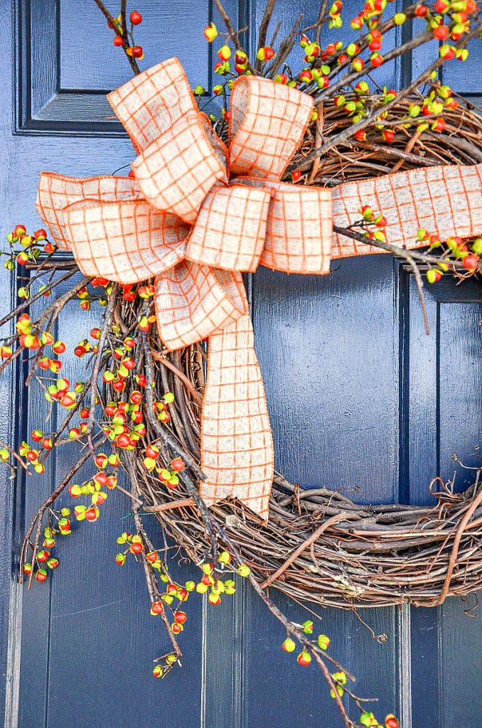 grapevine wreath with bittersweet and an orange and white checked bow