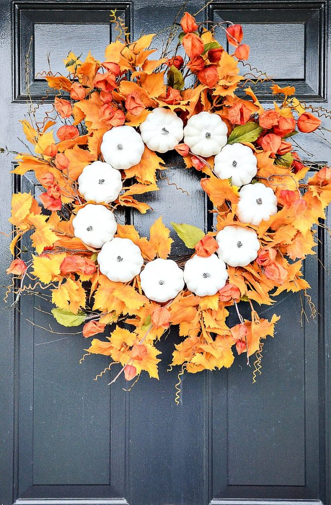 gorgeous orange leaves and Chinese lanterns on a fall wreath with little white pumpkins
