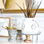 BUFFET DECORATED FOR FALL WITH A WHITE POTTERY CONTAINER WITH PHEASANT FEATHERS IN IT