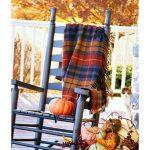 rocking chair on a porch with pumpkins a tartan and other fall decor
