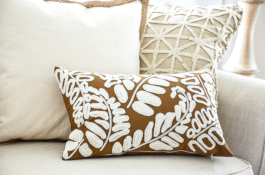 trio of neutral fall pillows on a white sofa