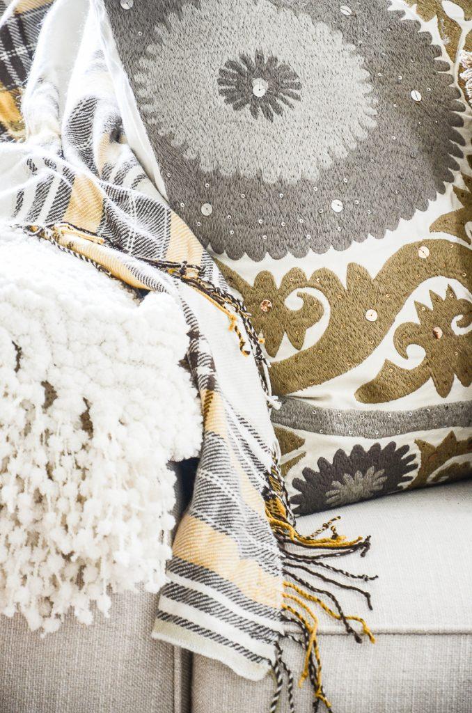 close-up of fall pillows and a tartan throw