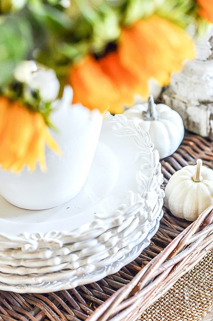 stack of white dishes in a fall vignette