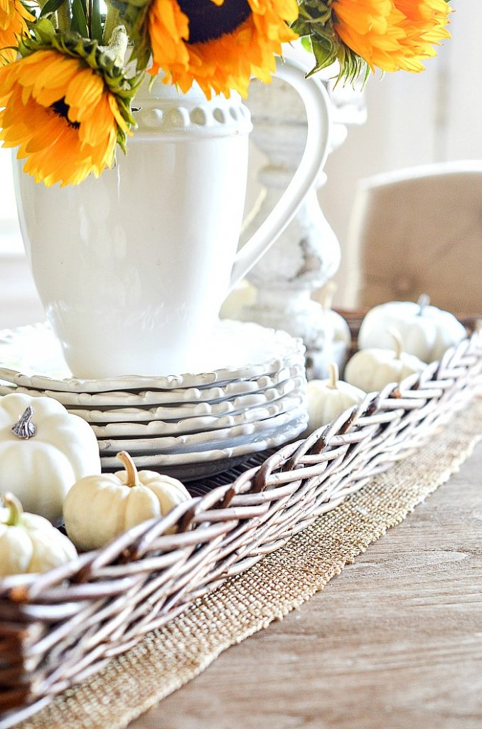 long wicker basket holding a fall vignette on a kitchen table