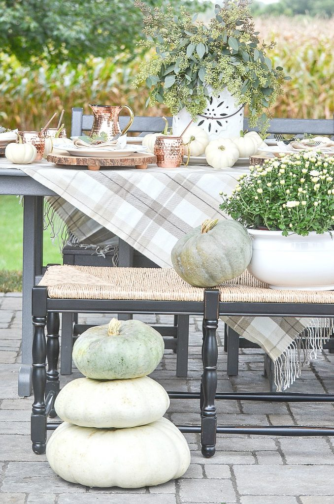 outdoor table decorated for fall with copper mugs, white pumpkins and mums