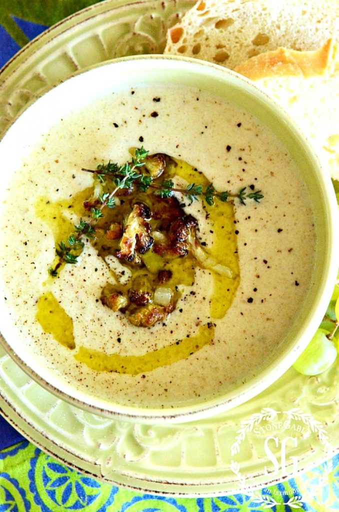 pretty cauliflower cheddar soup topped with olive oil and roasted cauliflower
