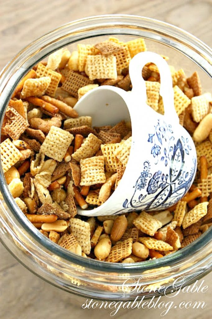 chex mix in a big glass canister with a cup to scoop out the mix