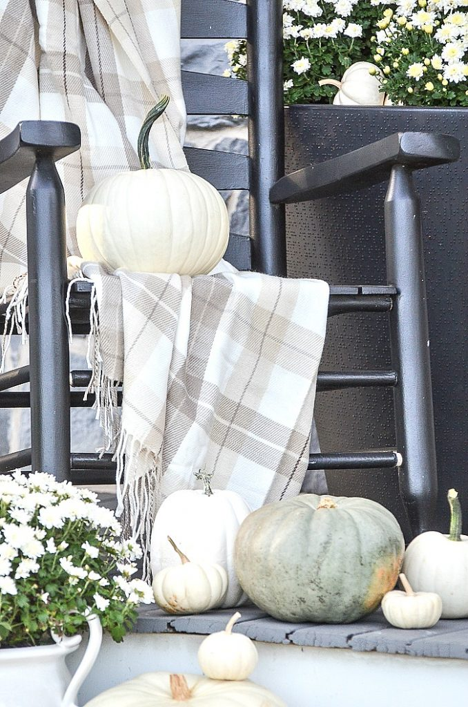 black rocker on a porch with a tartan throw over it and a pumpkin on the seat