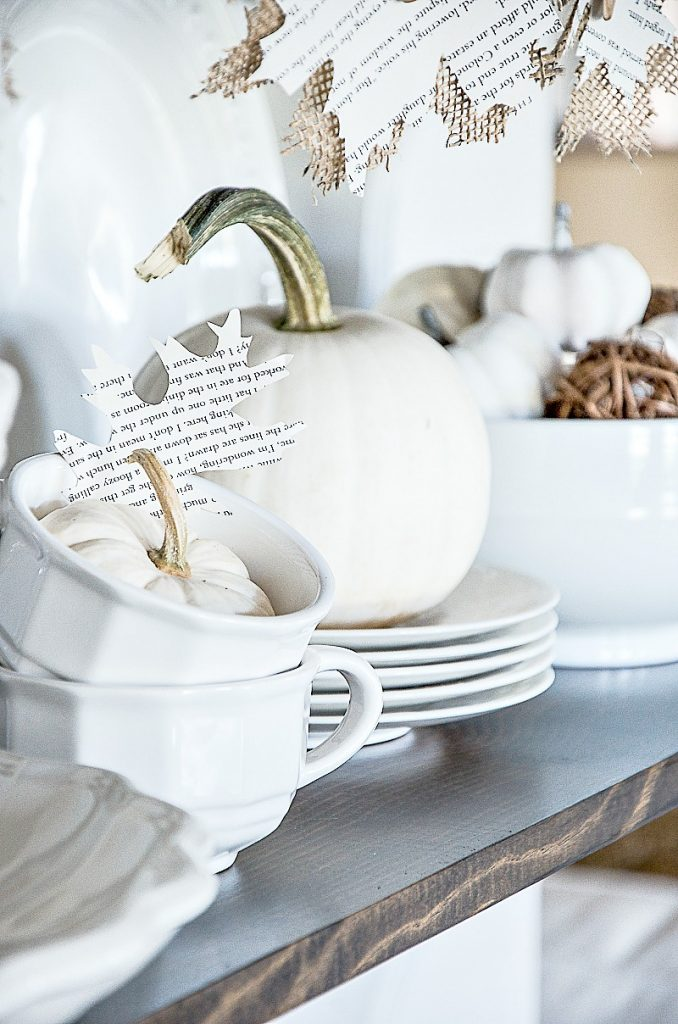 WHITE PUMPKINS ON A SHELF WITH WHITE DISHES