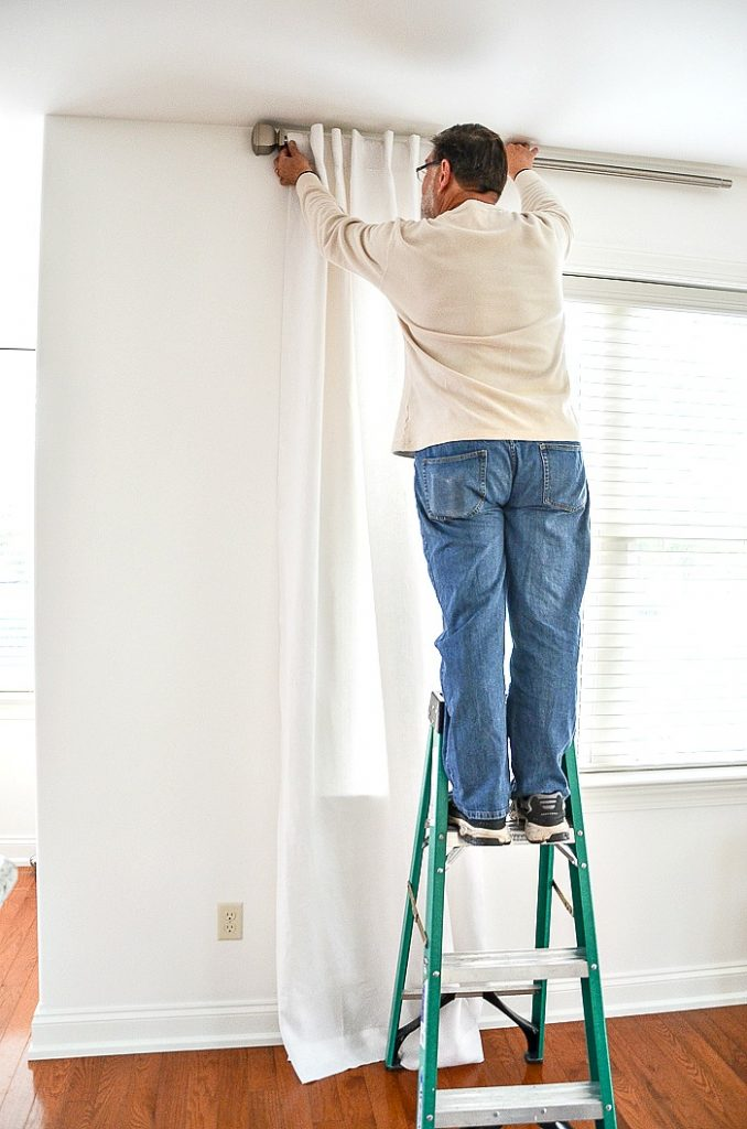 man hanging a white linen curtain