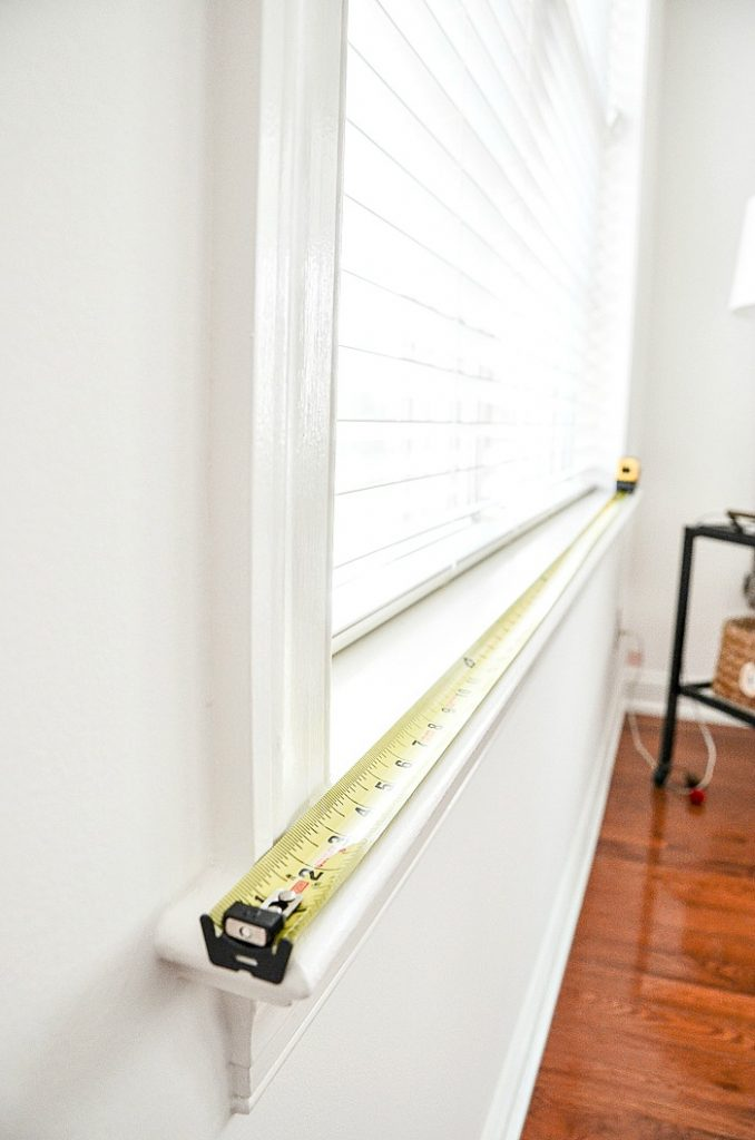 tape measurer along the sill of a window
