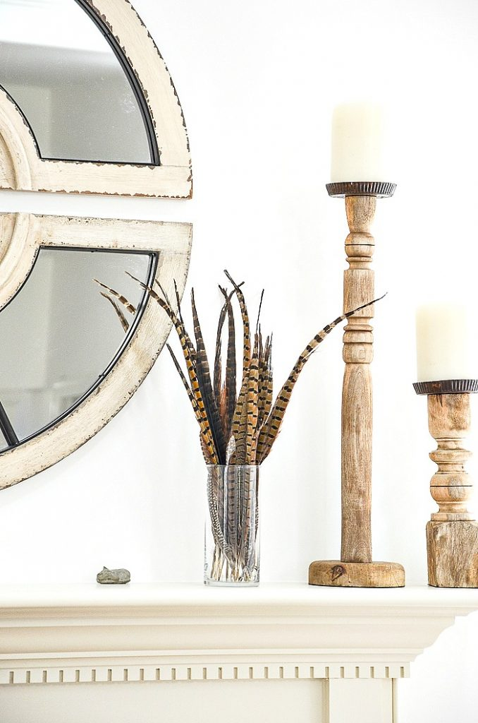 candlesticks and a round glass cylinder filled with pheasant feathers
