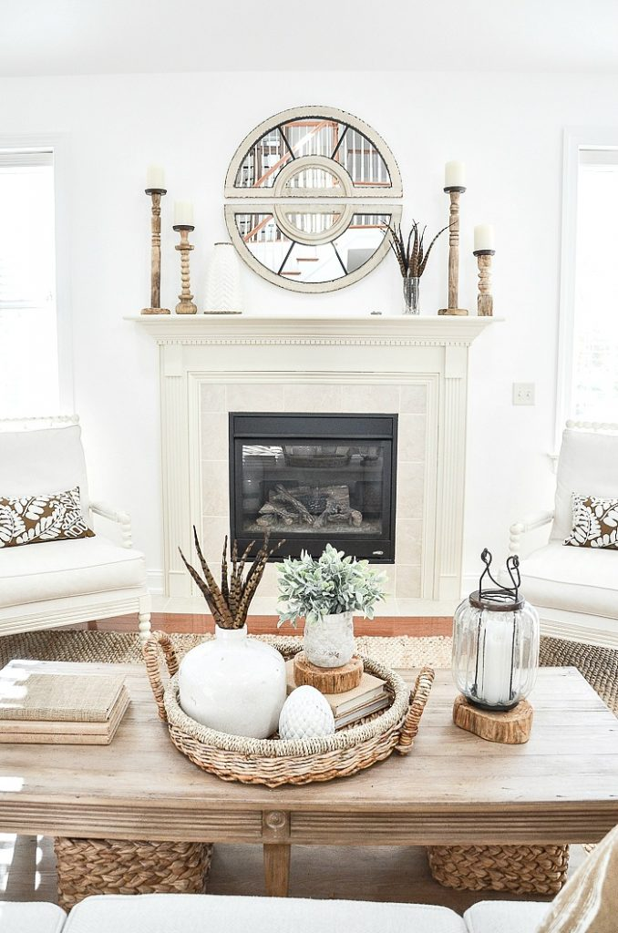 coffee table with books, lantern and a fall vignette in a basket