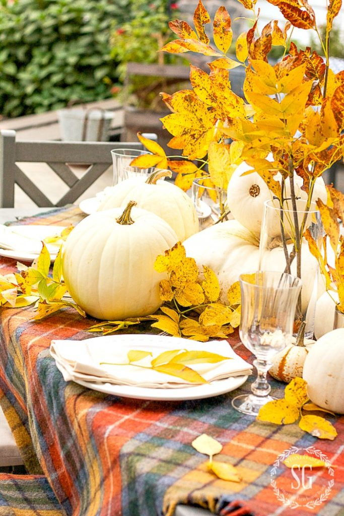 outside Thanksgving table set with pumpkins and white plates. EAsy thanksgiving tips