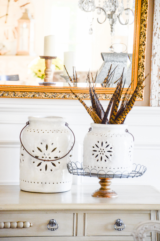 TWO WHITE LANTERNS WITH PHEASANT FEATHERS IN ONE