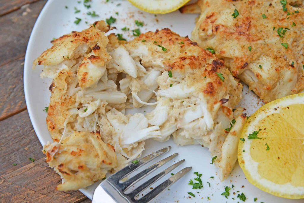 crab cakes on a white plate with lemon