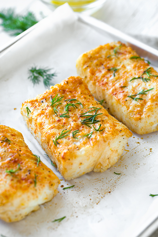 baked halibut on a baking sheet garnished with dill