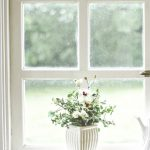 vase of white flowers in a window