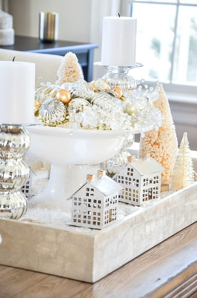arrangement of Christmas houses and candles on a coffee table