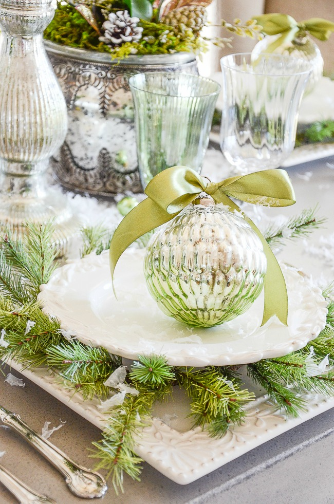 small green wreaths used as chargers under white dishes on a Christmas table
